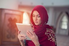 Beautiful young woman with tablet computer inside mosque.  Stock Photo