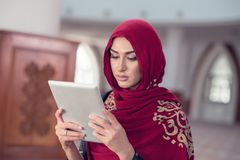 Beautiful young woman with tablet computer inside mosque.  Royalty Free Stock Photography