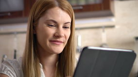 Beautiful young woman with a tablet sitting in kitchen. Browsing Internet and smiling. stock footage