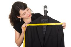 Beautiful young woman tailor measuring a black Royalty Free Stock Photos