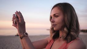 Beautiful young woman takes pictures on a smartphone in a dress posing walks along the coast smiling at sunset near the stock video footage
