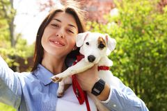 Beautiful young woman takes selfie with her cute jack russell terrier puppy on picnic in park, green grass & foliage background. F royalty free stock photo