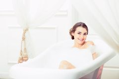 Beautiful young woman taking a bath Stock Images