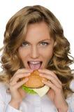 Beautiful young woman taking bite of hamburger Stock Photography