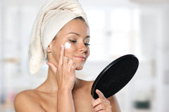 Beautiful young woman taking care of her skin Royalty Free Stock Photos