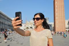 A beautiful young woman taking herself a selfie in Venice, Italy Royalty Free Stock Image