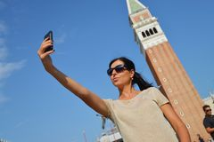 A beautiful young woman taking herself a selfie in Venice, Italy Royalty Free Stock Photography