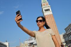 A beautiful young woman taking herself a selfie in Venice, Italy Stock Image