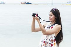 Beautiful young woman taking photo with camera mirrorless on the beach. Happy island lifestyle. Blue cloudy sky and crystal sea of stock photography