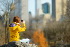 Beautiful young woman taking a photo of skyscapers Royalty Free Stock Images