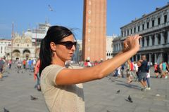 A beautiful young woman taking a photos with her smartphone in Venice Stock Photography