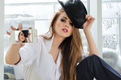 Beautiful young woman taking picture of herself on mobile Royalty Free Stock Images