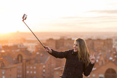 Beautiful young woman taking a picture with a selfie stick at sunset. City background. Urban and lifestyle. Casual clothing stock photo