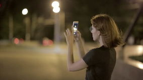 Beautiful young woman taking picture on smartphone at night street