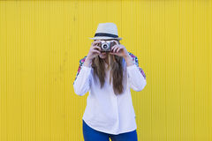 Beautiful young woman taking a picture with a vintage camera. Ye Stock Photo