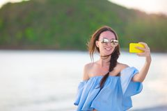 Beautiful young woman taking a self photo herself on tropical beach. Beautiful young woman taking a photo herself on tropical beach Stock Images