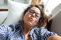 Beautiful young woman taking a selfie at home. Royalty Free Stock Image