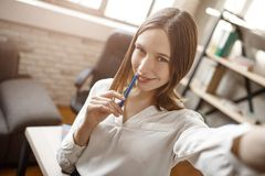 Beautiful young woman taking selfie in room during break. She pose and smile. royalty free stock photo