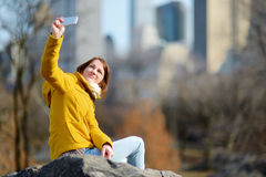 Beautiful young woman taking a selfie while sitting on a rock in Central Park Stock Image