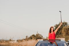 Beautiful young woman taking a selfie on top of a the car on a sunny day. Travel and fun concept.  stock images