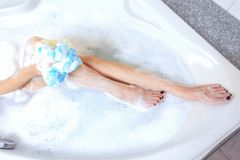 Beautiful young woman taking a shower. Hot bath tub and rest for. Her legs Stock Images