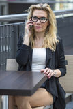 Beautiful young  woman talking on cell phone while sitting at a table. Royalty Free Stock Image