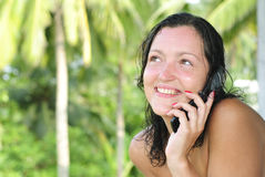 Beautiful young woman talking on cellphone. Beautiful young woman with big smile talking on the phone outdoors. Palm trees and paradise in the background Stock Images