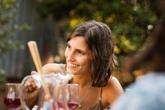 Beautiful young woman talking with friends Royalty Free Stock Photography