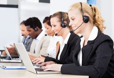 Beautiful young woman talking on headset Royalty Free Stock Photos