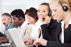 Beautiful young woman talking on headset Stock Photos