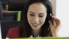 Beautiful young woman talking on headset in office call centre