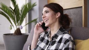 Beautiful young woman talking on mobile phone at home. Relaxed woman at cellphone sitting on couch. Happy girl talking stock video footage