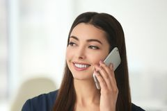 Beautiful young woman talking by mobile phone. Indoors Stock Photo