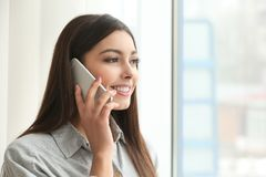 Beautiful young woman talking by mobile phone. Indoors Royalty Free Stock Image