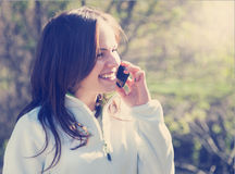 Beautiful young woman talking on mobile phone and smiling Royalty Free Stock Image