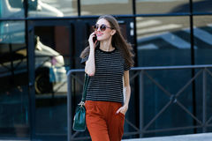 Beautiful young woman talking on mobile phone in the street. Royalty Free Stock Photo