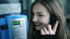 Beautiful young woman talking on payphone stock video