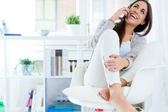 Beautiful young woman talking on the phone at home. Royalty Free Stock Photography