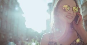 Beautiful young woman talking on phone during sunny day. Young girl enjoying sunny day and using phone stock footage