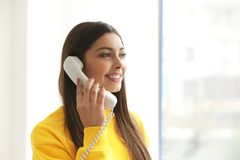 Beautiful young woman talking by telephone. Indoors royalty free stock photography