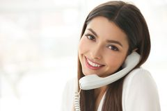 Beautiful young woman talking by telephone in office stock image