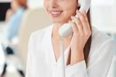 Beautiful young woman talking by telephone while working in office, closeup stock photo