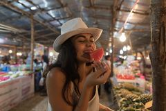 Beautiful Young Woman Tasting Watermelon On Traditional Street Market In Asia Girl Tourist Buying Fresh Fruits On. Thailand Bazaar Concept Royalty Free Stock Photos