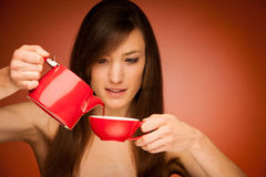 Beautiful young woman with tea pot and mug in her nhands Stock Images