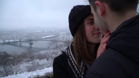 Beautiful young woman with teeth braces and man looking into each other`s eyes near river in winter clothing. Happy stock footage