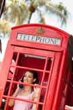 Beautiful young woman in telephone booth. Beautiful young woman in a vintage red telephone booth along Lincoln Road mall in Miami Beach Royalty Free Stock Image