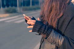 Beautiful young woman texting in the city streets Royalty Free Stock Photo