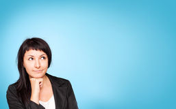 Beautiful young woman think. Blue background. Stock Photography