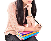 Beautiful young woman thinking on the pile of books Stock Photo
