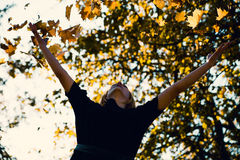 Beautiful young woman throwing autumn leaves Royalty Free Stock Photos